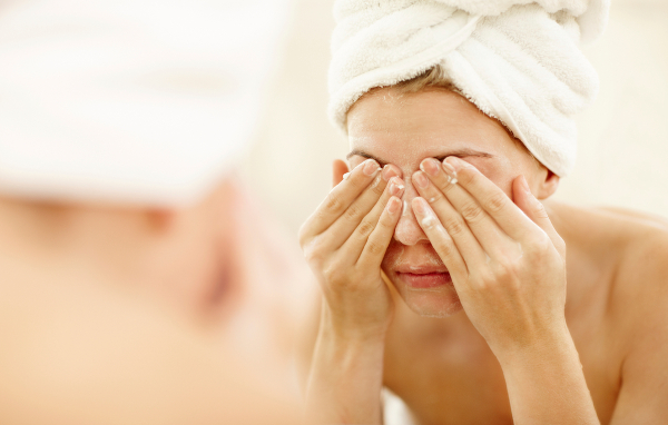Young caucasian woman cleaning and scrubbing her face with soap/facewash
